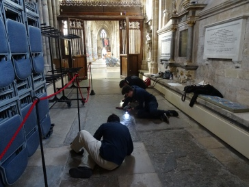 Students reading worn inscriptions using a torch